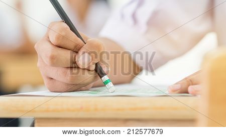 Students holding pencil eraser while taking exams examination room writing answer optical form in high school classroom view of having test in class on seat rows Education literacy concept.