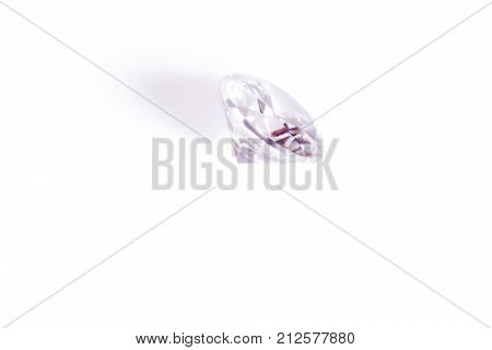 faceted diamond of violet color in macro on a white background