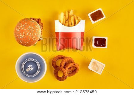 Fast food dish top view. Meat burger, potato chips and wedges. Take away composition. French fries, hamburger, mayonnaise and ketchup sauces on yellow background. Menu or receipt background. Top view. Copy space. Still life. Flat lay.