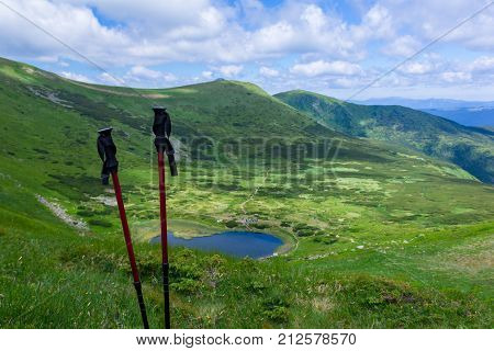tourist sticks against the background of a panorama of mountains with the lake and sky