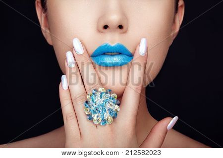 Beauty Fashion woman lips with natural Makeup and white Nail polish. Gloss Blue Lipstick. Beauty girl face close up. Sexy Lips Manicure Make up. Ring with Precious Stones Jewelry