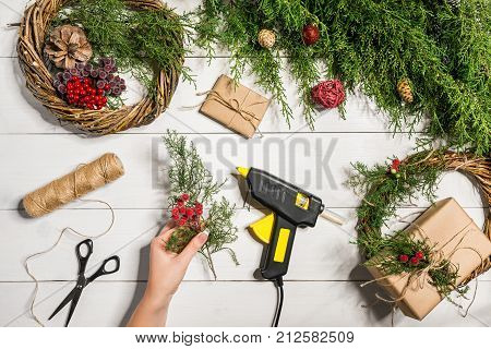 Christmas handmade diy background. Making craft xmas wreath and ornaments. Woman's leisure, tools and trinkets for holiday decorations. Top view of white wooden table with female hands.