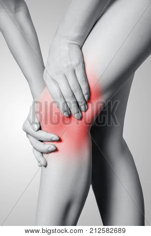 Closeup View Of A Young Woman With Knee Pain On Gray Background.