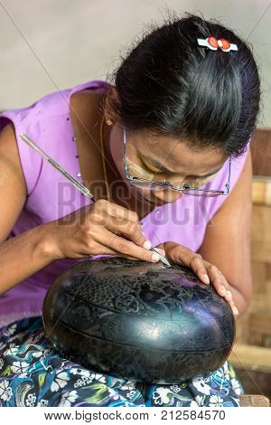 Bagan, Myanmar - October 13, 2016: Burmese woman working in a factory of lacquer in Bagan, Myanmar. Lacquerware includes boxes, tableware, buttons, plates etc