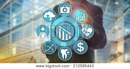 Unrecognizable data manager operating an analytics application designed to monitor healthcare cost reduction. Information technology concept for health care improvement via data analysis software.