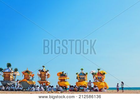 Bali Island Indonesia - March 18 2015: Balinese people procession rest after walking with hindu shrines to beach for traditional water purifying ceremony Melasti before celebration silence day Nyepi