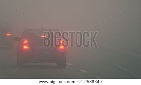 Cars In The Fog. Bad Winter Weather And Dangerous Automobile Traffic On The Road. Light Vehicles In