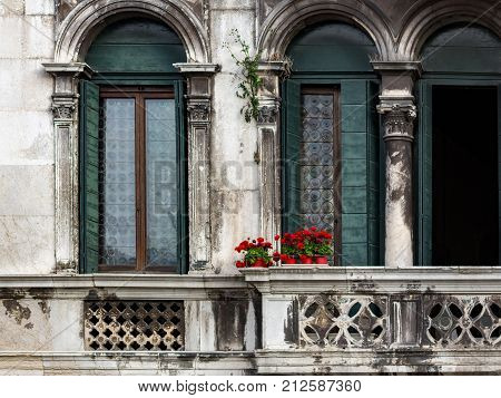 Venetian balcony. Venetian architecture. Ancient balcony in Venice, Italy. Balcony with red flowers. Red flowers in red pots against the background of a vintage building in Venice, Italy.