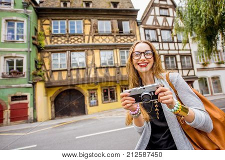 Young woman tourist standing with photo camera in front of the beautiful half-timbered houses traveling in Strasbourg city, France