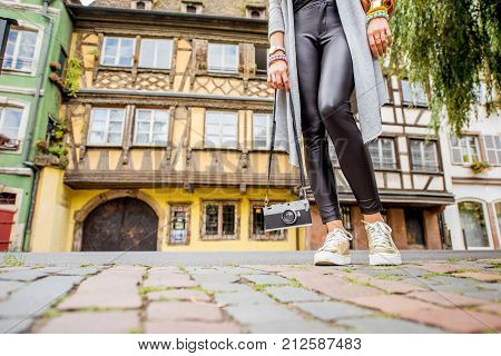 Woman holding photo camera on the steet with beautiful half-timbered houses traveling in Strasbourg city, France