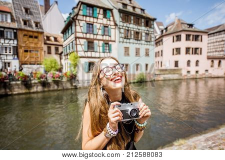 Young woman tourist standing with photo camera with beautiful old buildings and water chanal in Strasbourg city in France