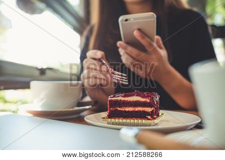 Closeup image of a woman holding using and looking at smart phone while eating a cake with white coffee cups and laptop on wooden table in vintage cafe