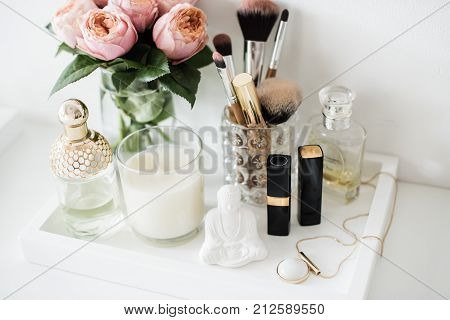 Ladys dressing table decoration with flowers, beautiful details, luxurious perfumes and makeup tools. White expensive interior decor closeup.