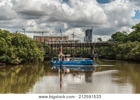 Parramatta Australia - March 24 2017: Australian Environmental Services cleans debris and trees out of the Parramatta River near the city using blue painted boat with crane and slipway.