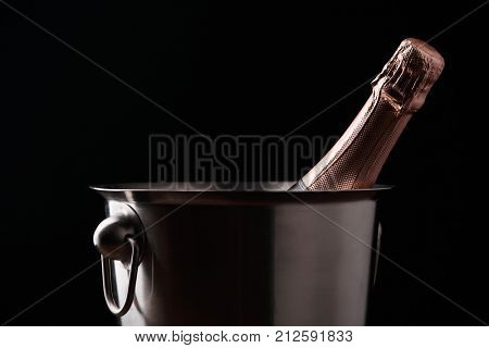 Photo of bottle of champagne in iron bucket