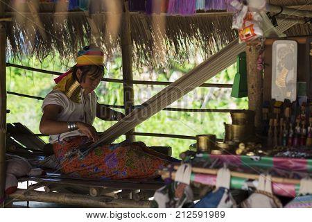 CHIANG RAI, THAILAND - NOVEMBER 4 2017: Unidentified Long Neck Karen hill tribe woman selling folk art goods and making cotton canvas.