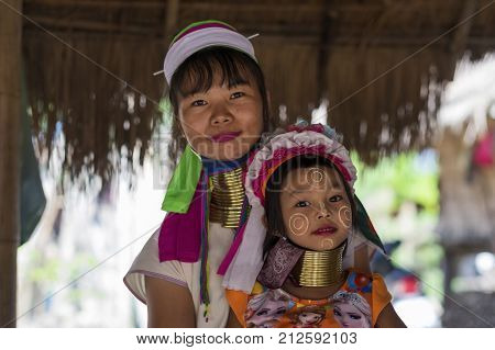 CHIANG RAI, THAILAND - NOVEMBER 4 2017: Unidentified Long Neck Karen hill tribe people. Mother anf daughter smiling at camera. A unique mountain tribe in the tourist village