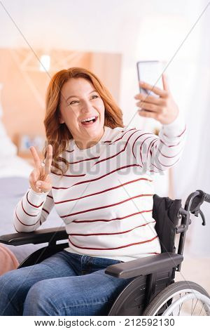 Having fun. Attractive alert blond crippled woman smiling and taking photos while sitting in a wheelchair and showing the peace sign with her fingers