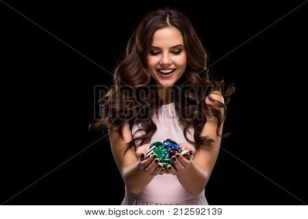 Sexy woman in a chic gently pink dress holding colored poker chips on a black background. Woman winning. Casino. Poker. Victory. Luck