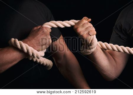 The fight of two men with a tug of war. Tug-of-war