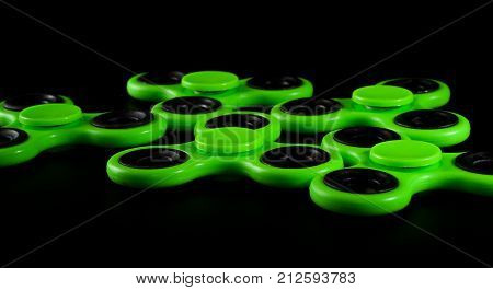 Green fidget spinners - stress relieving toys on a black background