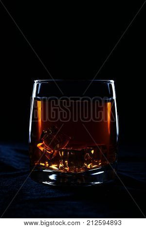 Glass of whiskey with ice cubes on black background. Image on low key.