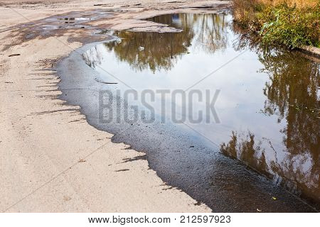 Puddles After Rain. Reflection Of Sky And Buildings In Puddles. Cracked Asphalt Texture