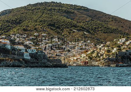 Saronic sea view of the panorama that we find when arriving at the port of the island of hydra with the entrance to it the city and the mountain in the background. Port that historically was fishing today lives of tourism.