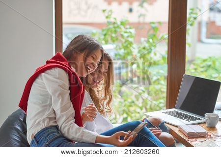Shot of two young women laughing happily taking selfies at the cafe copyspace technology positivity 3g 4g online internet smart phone bonding students educational project startup.