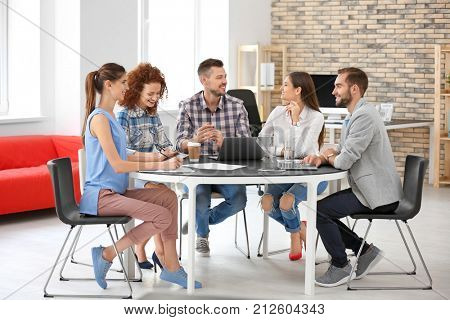 Team of young professionals conducting business meeting in office
