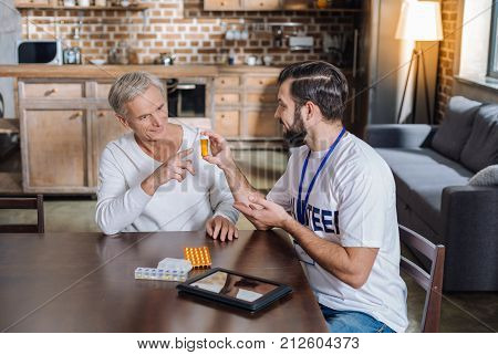 Try it. Kind clever friendly social worker looking cheerful while persuading a senior man to try new progressive medicine