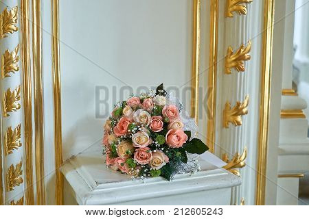 Beautiful wedding bouquet in rustic style with roses on gold background