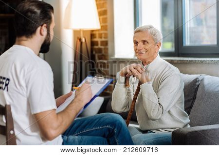 Funny story. Cheerful kind senior man looking satisfied while telling a funny story to his attentive young volunteer