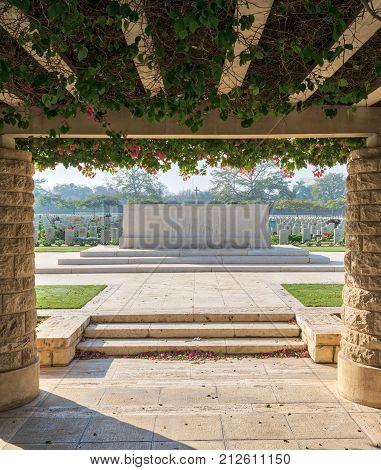 Entrance of Heliopolis Commonwealth War Cemetery with two stone bricks columns and climber green plants Cairo Egypt