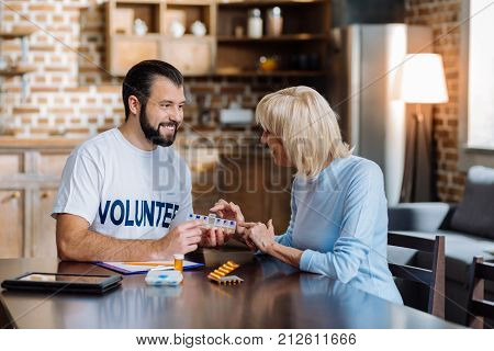 Convenient thing. Pleasant reliable attentive volunteer sitting and smiling while showing a convenient pill box to a curious senior woman