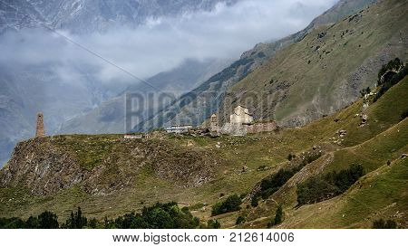 Georgia. An ancient church and a watchtower in the background of the mountains near the Georgian Military Road in the Gudauri district.