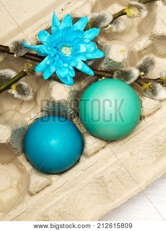 Easter background with eggs and catkins on white wooden background copy space