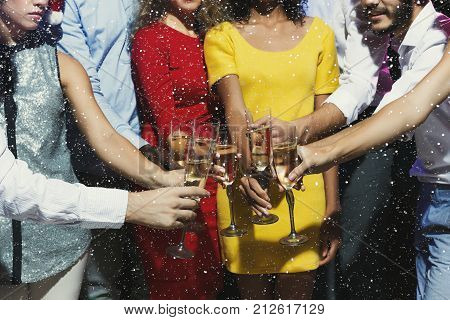 Christmas party time. Young people toasting with champagne flutes. Multiethnic friends congratulating each other with new year. Celebration and nightlife concept, holiday background, crop