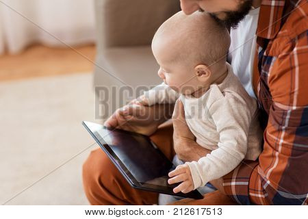 family, parenthood and people concept - happy father and little baby boy with tablet pc computer at home