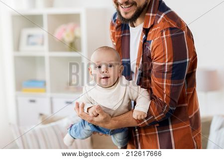 family, parenthood and people concept - close up of happy father playing with little baby boy at home