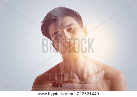 Lonely road. Handsome wistful serious guy feeling lonely on the life road  looking hopeless with his shoulders lowered on the grey background
