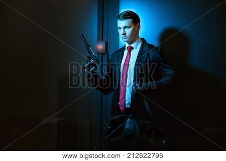 Professional man is a murderer in his hand a pistol with a silencer.