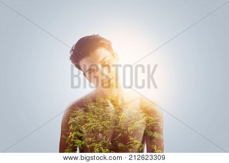 Nature is inspiration. Handsome strong peaceful guy searching for ides in nature looking adorably standing against the grey background