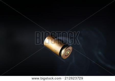 Empty bullet shell casings on a black background smoke.