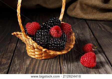 Raspberries and blackberry in a small basket that stands on old boards