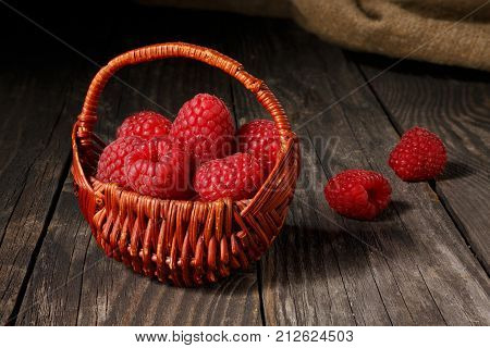 Raspberries in a small basket that stands on old boards