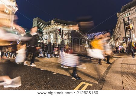 People crossing street in Oxford Circus London. It is Christmas time and there are many decorating lights over the streets. Travel holidays and shopping concepts.