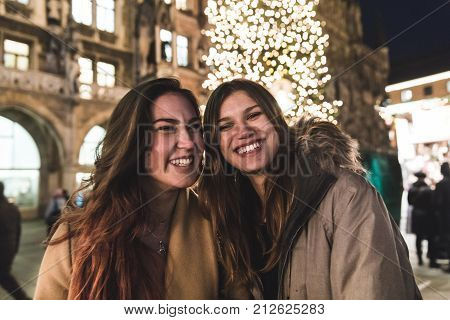 Teenage Girls And Friends Smiling With Christmas Tree On Background