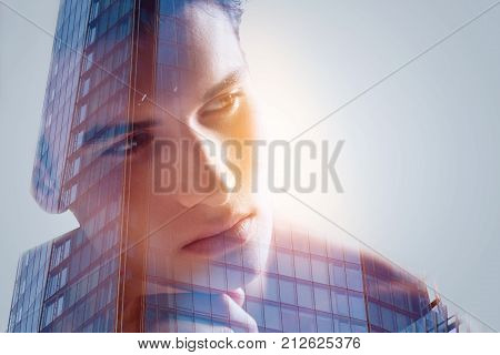 Waiting for. Close up portrait  of promising attractive chap looking aside posing agains office building  who placing his hand under chin