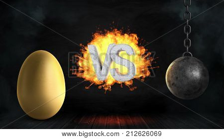 3d rendering of a large concrete letters VS on fire stand between a large golden egg and a black iron wrecking ball. Golden goose. Profitable business. Risk and danger.